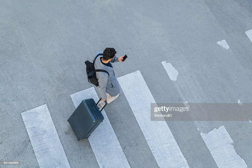 Businessman with baggage crossing the street while looking at cell phone, top view : Stock Photo