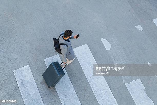 Businessman with baggage crossing the street while looking at cell phone, top view