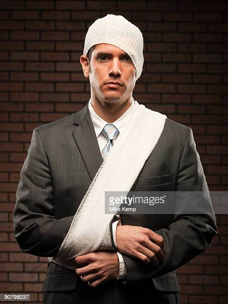 businessman with bandages on - workers compensation stock pictures, royalty-free photos & images