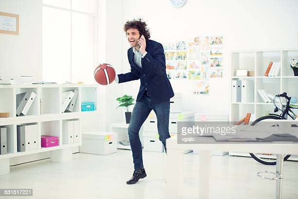 Businessman with basketball in office.