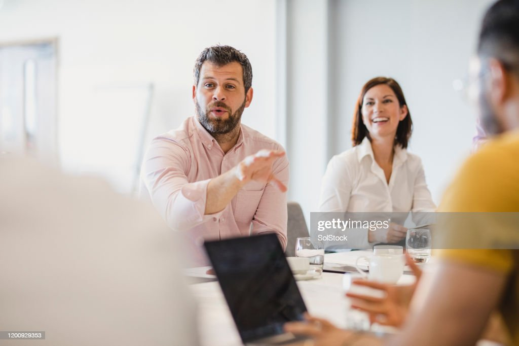 Businessman with beard explaining in meeting with colleagues : Stock Photo