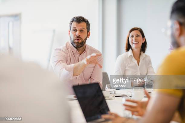 businessman with beard explaining in meeting with colleagues - employee engagement stock pictures, royalty-free photos & images