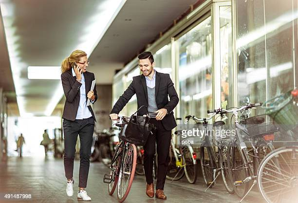 Homme d'affaires en vélo et collègue marchant sur la rue