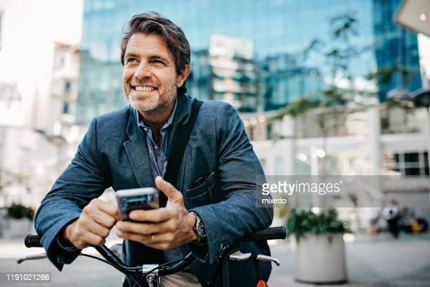 businessman with bicycle and mobile phone in city - 45 49 years stock pictures, royalty-free photos & images