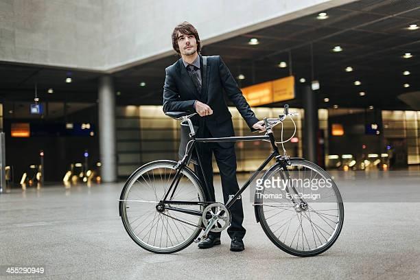 Geschäftsmann mit Fahrrad in der U-Bahn-station