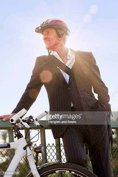 Businessman with bicycle on bridge
