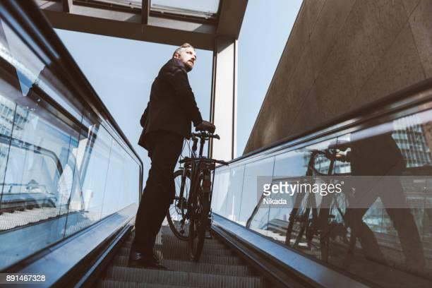 Geschäftsmann mit dem Fahrrad auf Rolltreppe