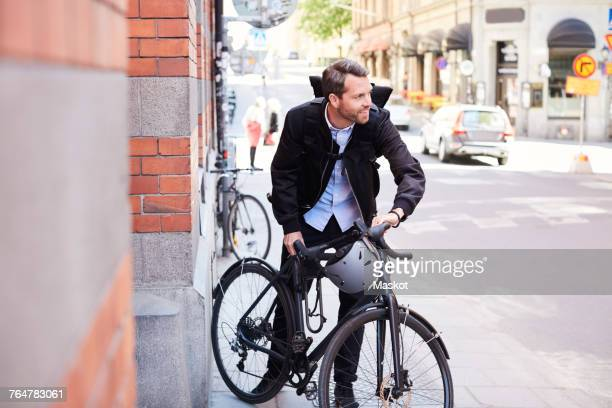 Businessman with bicycle on street in city during sunny day