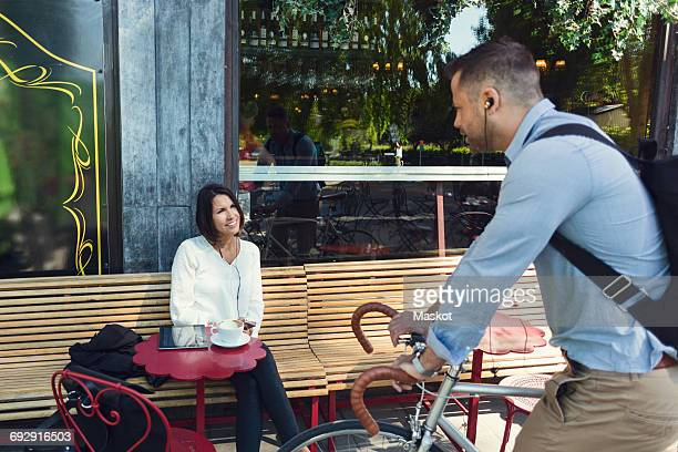 Businessman with bicycle talking to colleague sitting at sidewalk cafe