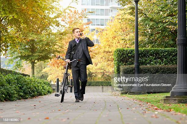 Businessman with bicycle using mobile phone