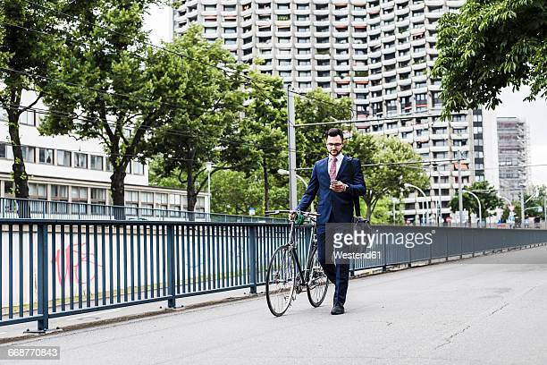 Businessman with bicycle walking in the city, using smart phone