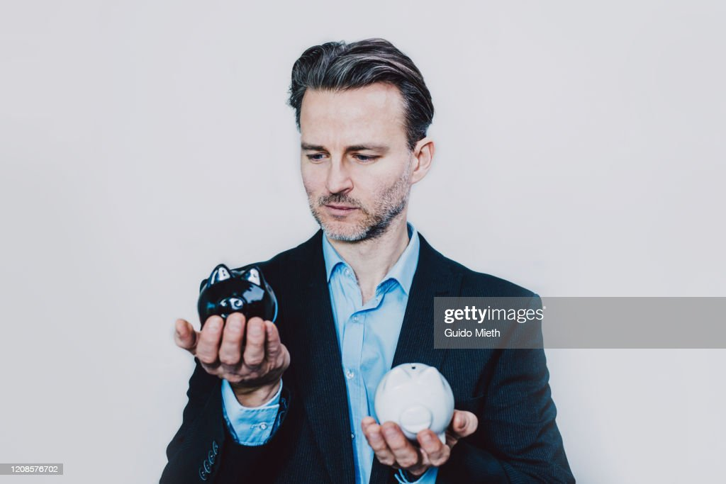Businessman with black and white piggy bank. : Stock Photo