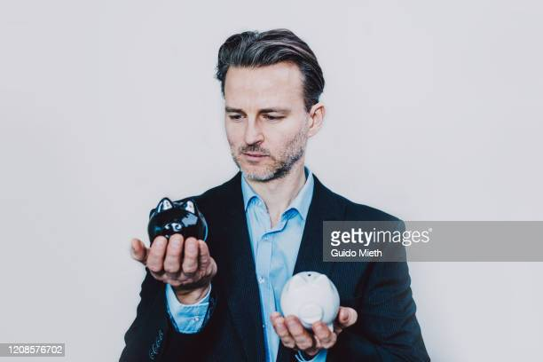 businessman with black and white piggy bank. - decisions stock pictures, royalty-free photos & images