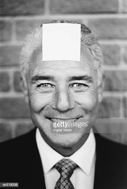 Businessman with blank paper on forehead