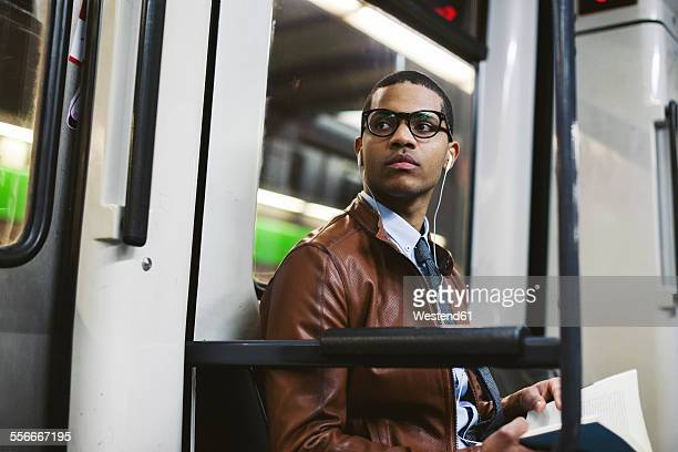 Businessman with book on the subway train