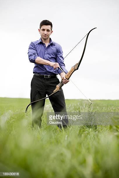 Homme d'affaires avec l'arc et flèche dans Prairie
