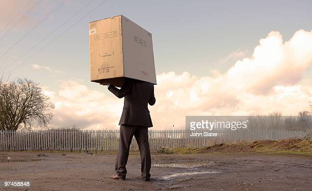 businessman with box on his head - newpremiumuk stock pictures, royalty-free photos & images