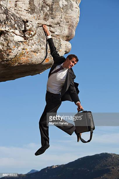 Businessman with briefcase clinging onto cliff