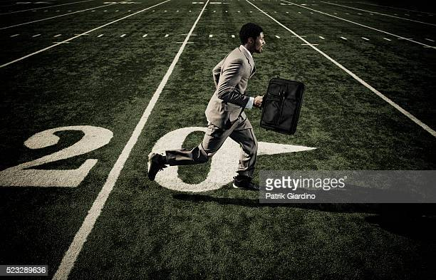 Businessman with Briefcase Running on Football Field