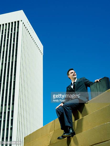 Businessman with briefcase sitting on steps outside office building