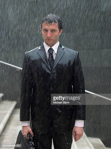 businessman with briefcase standing on steps in rain, portrait - bagnato foto e immagini stock