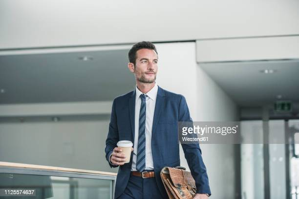 businessman with briefcase walking in office building, holding cup of coffee - cravatta foto e immagini stock