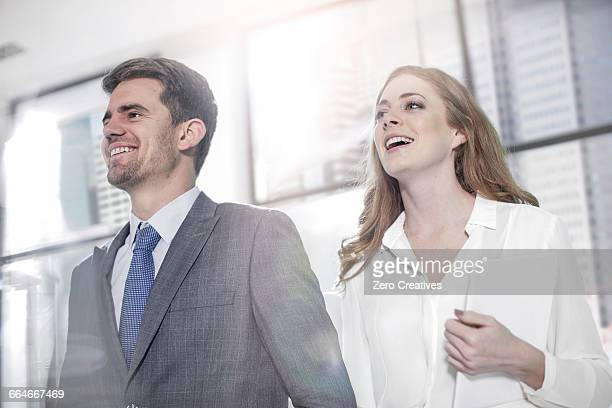 Businessman with businesswoman carrying digital tablet outside office building