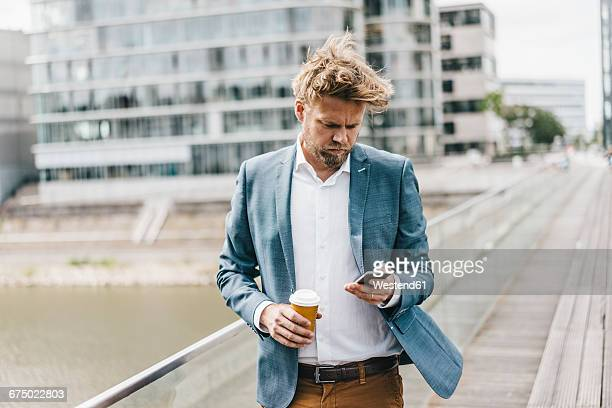 Businessman with cell phone and coffee to go on bridge
