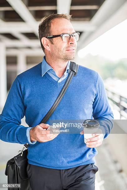 Businessman with cell phone and coffee to go on the move