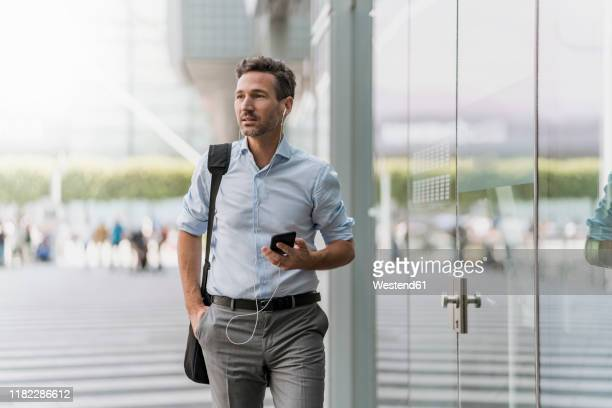 businessman with cell phone and earphones on the go - shoulder bag stock pictures, royalty-free photos & images