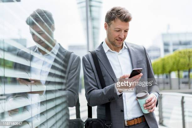 businessman with cell phone and takeaway coffee in the city - green suit stock pictures, royalty-free photos & images
