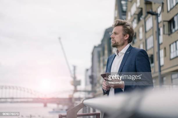businessman with cell phone at the riverside - köln stock-fotos und bilder