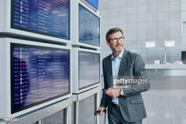 businessman with cell phone at timetable at the airport - ein mann allein stock-fotos und bilder
