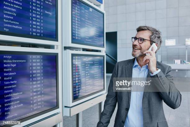 businessman with cell phone at timetable at the airport - flughafenterminal stock-fotos und bilder
