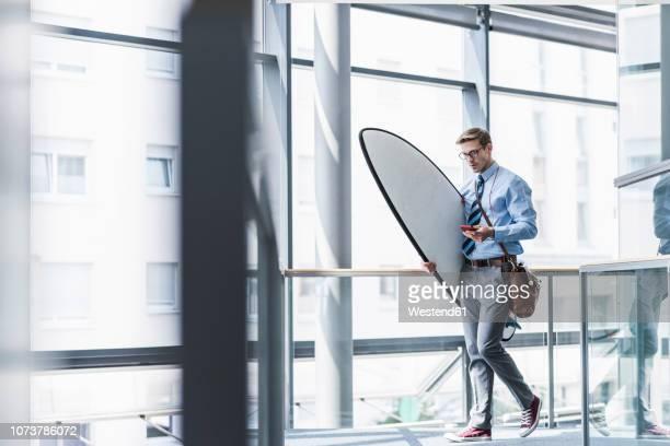 businessman with cell phone carrying surfboard in office - na werktijd stockfoto's en -beelden