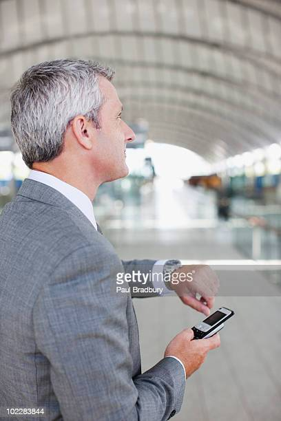 Businessman with cell phone checking the time