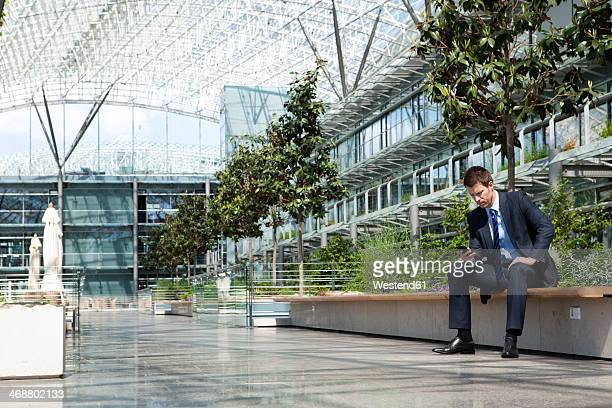 Businessman with cell phone in courtyard