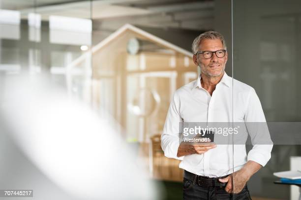 Businessman with cell phone in office