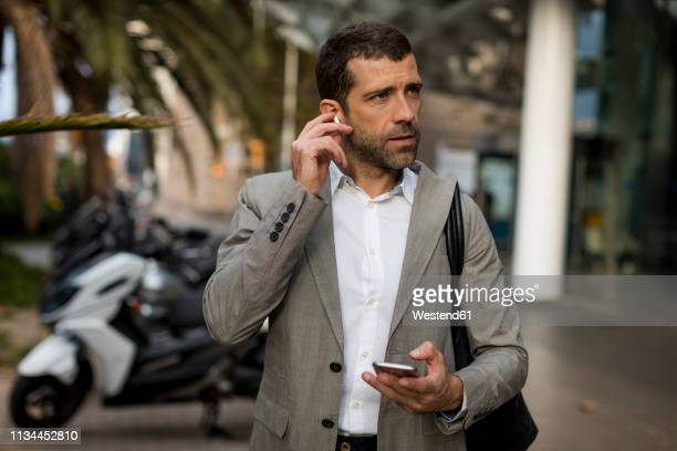 businessman with cell phone in the city applying earbuds - bluetooth stock pictures, royalty-free photos & images