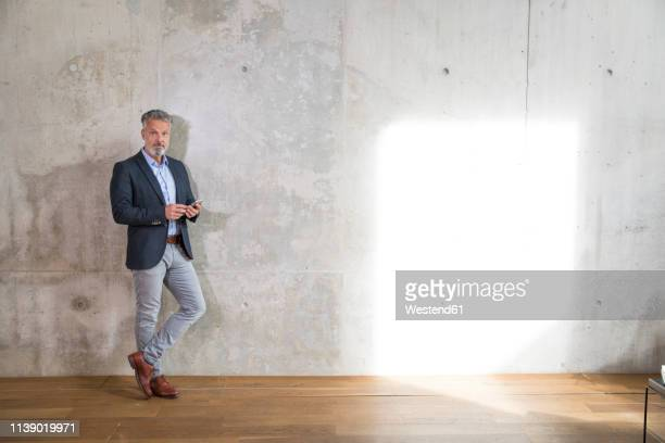 businessman with cell phone leaning against concrete wall in a loft - lehnend stock-fotos und bilder