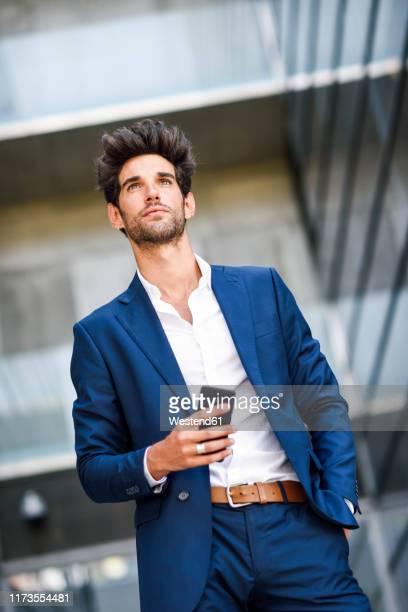 businessman with cell phone outside an office building - schrägansicht stock-fotos und bilder