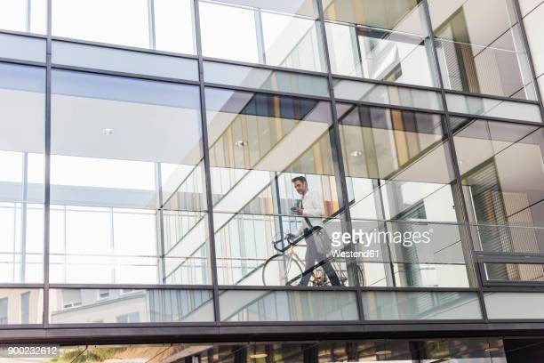 Businessman with cell phone pushing bicycle in office passageway