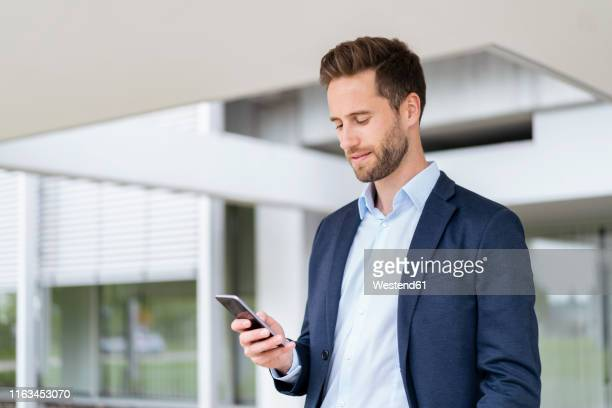 businessman with cell phone standing outdoors - abbigliamento elegante foto e immagini stock
