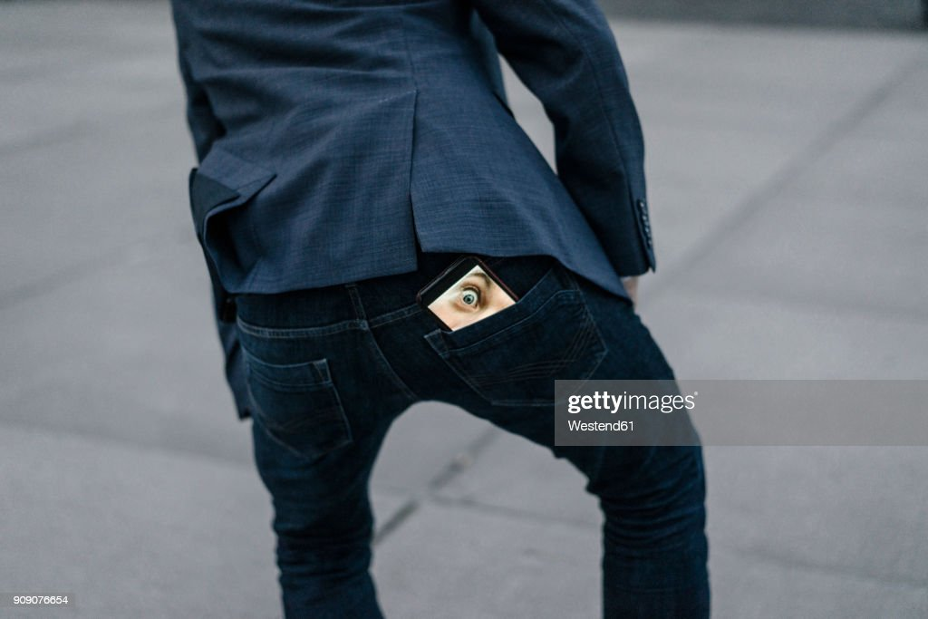 Businessman with cell phone with image of eyes in his trouser pocket : Stock Photo