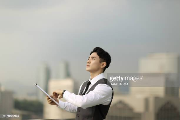 Businessman with clipboard looking up