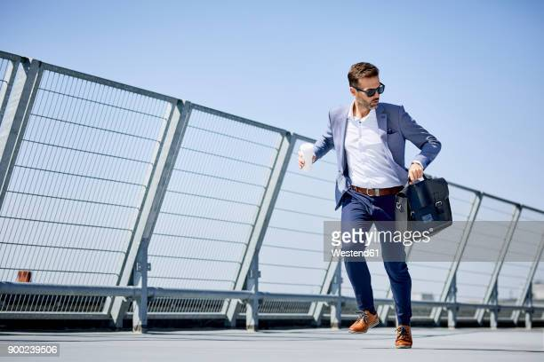 businessman with coffee and briefcase running - urgency stock pictures, royalty-free photos & images