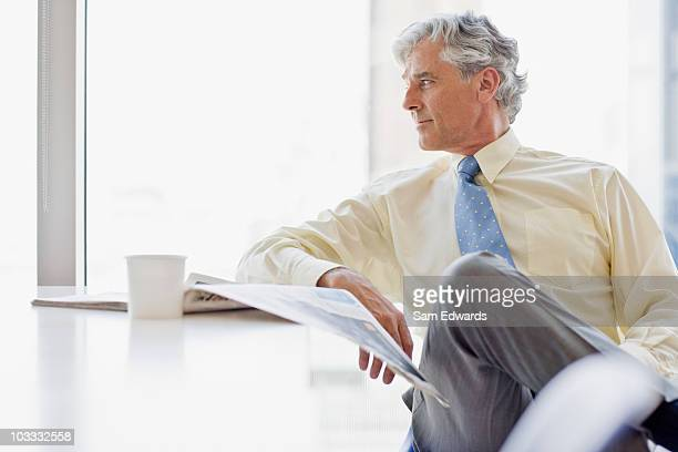 Businessman with coffee and newspaper looking away