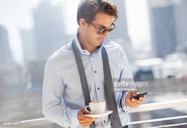 Businessman with coffee checking cell phone on urban balcony