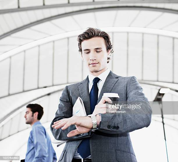 Businessman with coffee checking the time