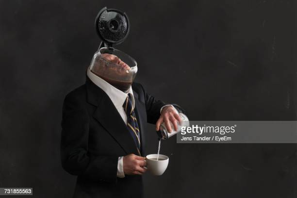 businessman with coffee maker on head pouring sugar in cup against black background - sugar coffee stock photos and pictures